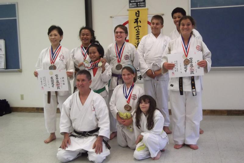 Joyful Karate family with 10th Taikai medals and menjos